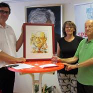 Ralf Hofmann und Kathi Petersen überreichen dem Jubilar Karl Rosentritt eine Karikatur